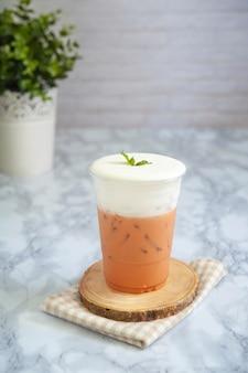 Tè al latte tailandese su crema di formaggio in vetro plastica.