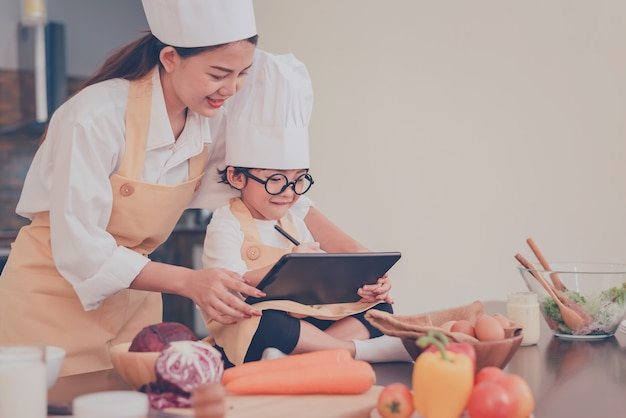Mamma tailandese e bambino che cucinano insieme a casa. distanziamento sociale e soggiorno a casa state al sicuro. attività familiare effetto da covid-19 e fermare il virus dell'epidemia. lock down e auto-quarantena a casa.
