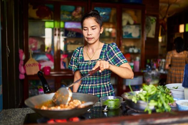 Madre tailandese che cucina curry rosso tradizionale nella cucina domestica rustica