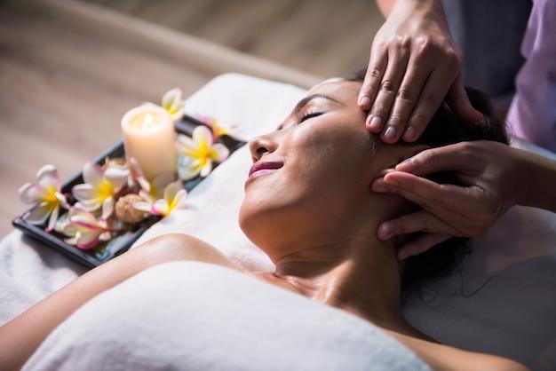 Massaggio facciale con olio tailandese sul letto alla bella giovane donna asiatica rilassante nel salone della stazione termale. assistenza sanitaria e relax per curare il concetto di dolore. settore sanitario alternativo.
