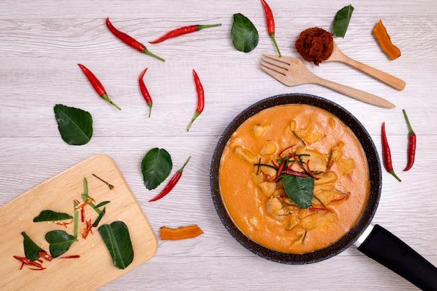 Pollo al curry tailandese pandan con foglie di lime kaffir verde e decorazione di peperoncino rosso.