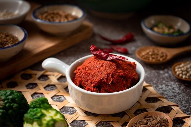Pasta piccante thai red - ingredienti alimentari tailandesi per cucinare curry rosso piccante a base di peperoncino essiccato, semi di coriandolo, scorza di lime kaffie, pepe bianco ed erbe locali