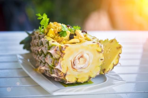 Riso tailandese con pollo in piatto di ananas con verdure sulla tavola di legno vista posteriore orizzontale