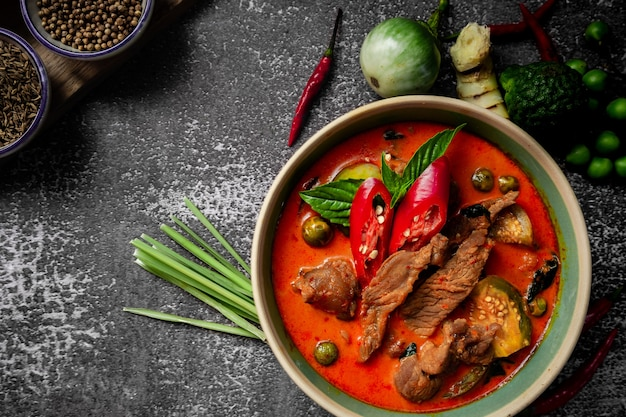 Curry rosso piccante tailandese con ingredienti di pasta di curry sul tavolo rustico - menu di cibo tailandese