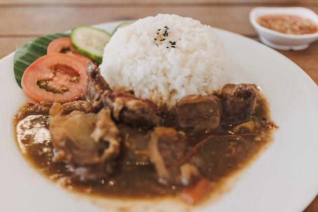 Stufato di manzo tailandese con riso servito su piatto bianco