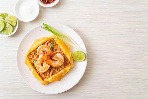 Tagliatelle fritte in padella thailandese con gamberetti e involucro di uova (pad thai), stile tailandese