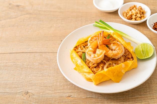 Tagliatelle fritte in padella thailandese con gamberetti e involucro di uova (pad thai) - stile tailandese