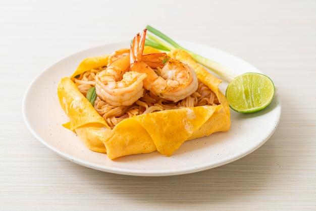 Spaghetti saltati in padella thailandese con gamberetti e involucro di uova (pad thai)