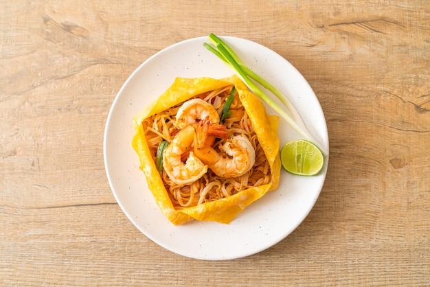 Tagliatelle saltate in padella thailandese con gamberetti e involucro di uova (pad thai)