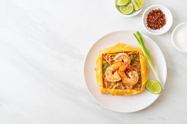 Tagliatelle fritte in padella thailandese con gamberetti e involucro di uova