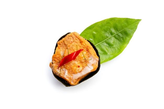 Curry di pesce in streaming tailandese in foglie di banana su foglia di noni o morinda citrifolia su sfondo bianco.