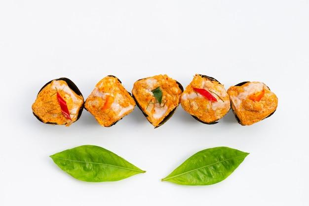 Curry di pesce in streaming tailandese in foglie di banana su foglie di noni o morinda citrifolia su sfondo bianco.