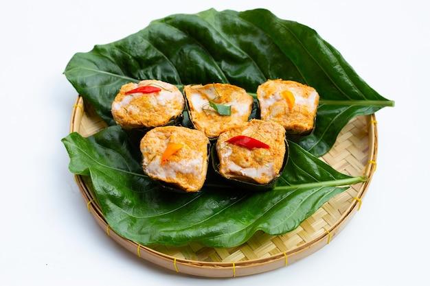 Curry di pesce in streaming tailandese in foglie di banana su foglie di noni o morinda citrifolia su superficie bianca