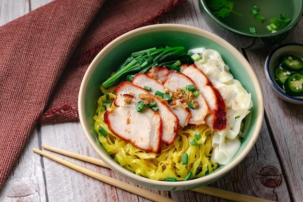 Cibo di strada tailandese - pasta all'uovo con maiale rosso alla brace e wonton servito con zuppa