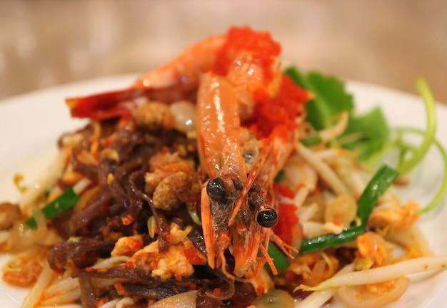 Tagliatelle di riso in padella stile tailandese saltati in padella o pad thai condita con gamberi serviti