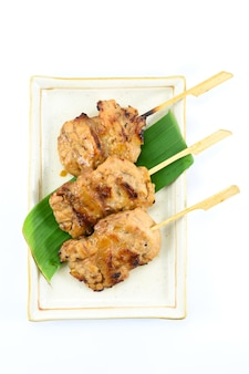 Barbecue di maiale in stile tailandese su un piatto e uno sfondo bianco