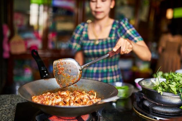Donna tailandese che cucina il curry piccante rosso del pollo nel wok