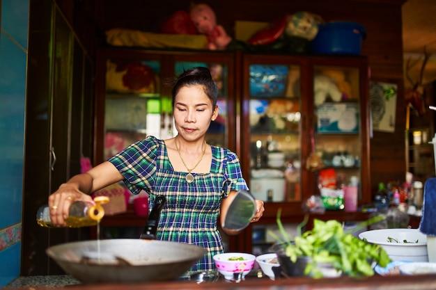 Donna tailandese versando olio nel wok nella tradizionale cucina domestica