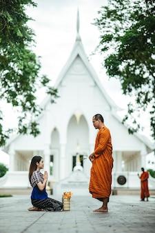 Donna tailandese con il vestito tradizionale che prega con il monaco