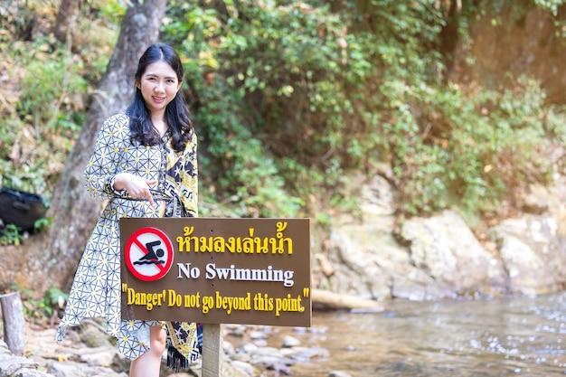Le donne tailandesi indicano il divieto di nuotare in questa contraddizione dell'area