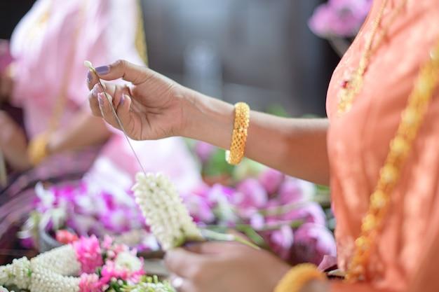 Le donne tailandesi in vestito tradizionale tailandese stanno decorando i fiori.