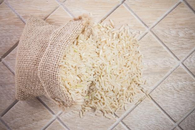 Riso al gelsomino della thailandia in sacchi su fondo di legno
