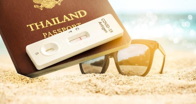 Passaporto thailandese e kit di test dell'antigene covid-19 con risultato del test negativo e occhiali da sole posizionati sulla spiaggia sabbiosa, concetto di vaccinazione del passaporto