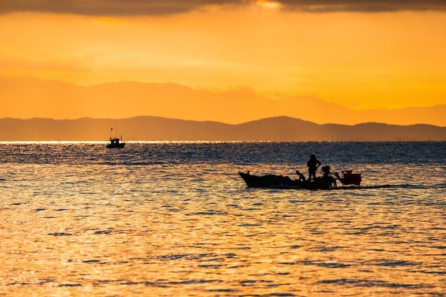 Il mare della thailandia al crepuscolo con la nave silhouette e il pescatore in mare