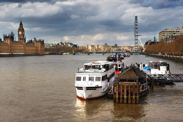Fiume tamigi e barche fluviali con famoso skyline di londra sotto il cielo drammatico