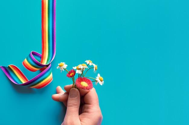 Grazie medici e infermieri! nastro arcobaleno su sfondo turqiouse. mano di donna con fiori di camomilla e primula, semplici simboli di ringraziamento.