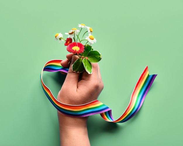 Grazie medici e infermieri! testo arcobaleno, nastro in mano di donna con fiori di camomilla e primula, bouquet semplice. creativo piatto disteso, vista dall'alto dall'alto