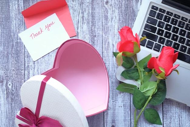 Messaggio di ringraziamento, busta, confezione regalo e fiore sulla tavola di legno