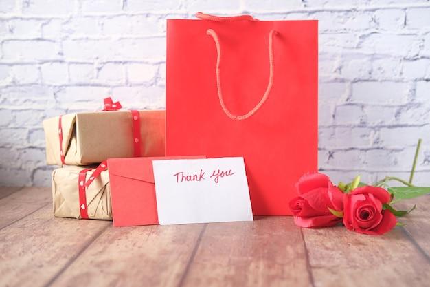 Messaggio di ringraziamento, confezione regalo e busta sul tavolo di legno