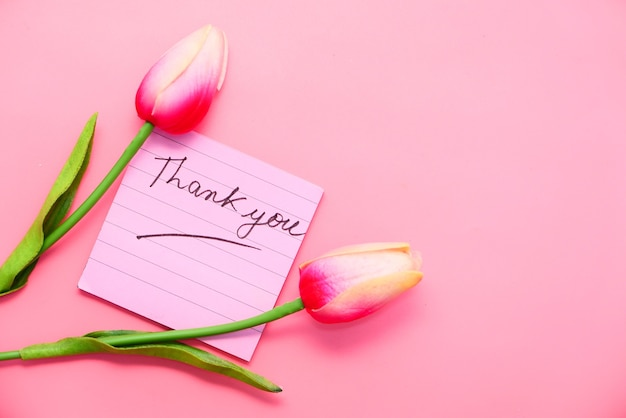 Messaggio di ringraziamento sulla nota adesiva con fiore di tulipano su sfondo rosa.