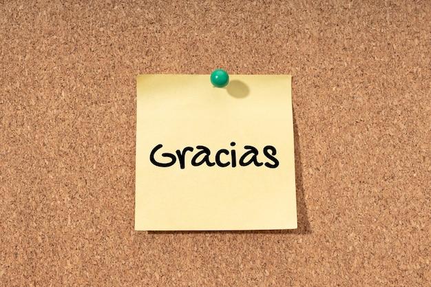 Grazie in spagnolo scritto su post-it giallo su sfondo di bacheca di sughero
