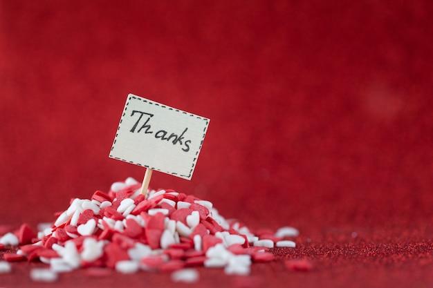 Grazie testo composto a bordo in un mucchio di cuori rossi e bianchi sulla parete rossa per il giorno di san valentino e il concetto di giorno di ringraziamento.