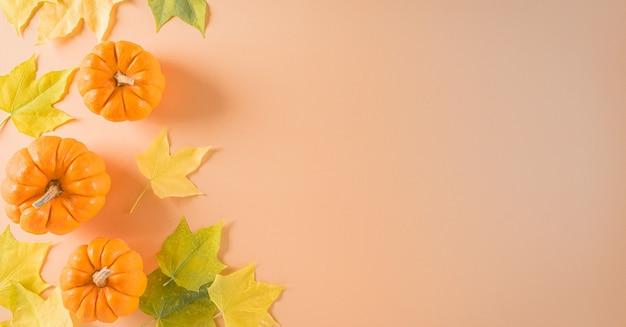 Decorazione di sfondo del ringraziamento da foglie secche e zucca su sfondo arancione pastello