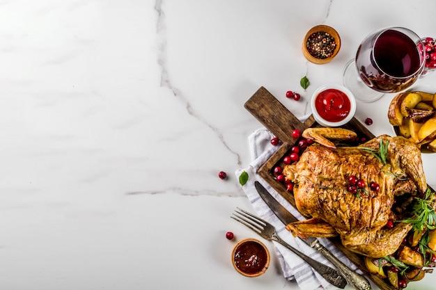 Cena del ringraziamento, pollo arrosto al forno con mirtilli rossi ed erbe aromatiche, servito con verdure fritte, vino di bacche fresche e salse sul tavolo di marmo bianco, vista dall'alto