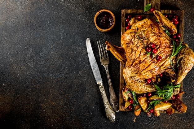 Cibo del ringraziamento, pollo arrosto al forno con mirtilli rossi ed erbe, servito con verdure fritte e salse sul tavolo scuro arrugginito, sopra