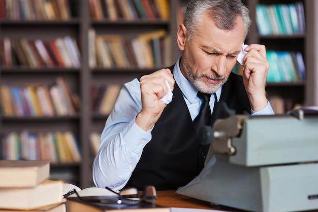 È tutto sbagliato! uomo anziano frustrato dai capelli grigi in abiti da cerimonia seduto alla macchina da scrivere e con pezzi di carta in mano con una libreria sullo sfondo