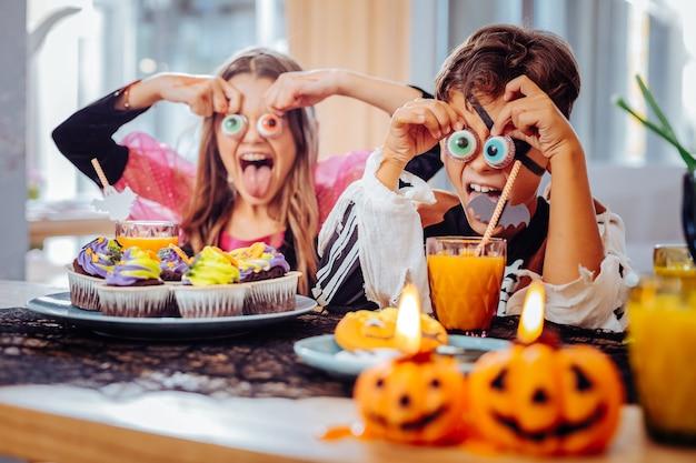 Cookie tematici. fratello e sorella divertenti di bell'aspetto che hanno festa di halloween divertendosi mentre mangiano i biscotti tematici