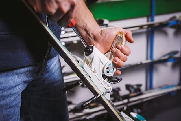 Tema tintura e riparazione sci attrezzatura da sci. primo piano della mano di un uomo caucasico utilizzare uno strumento di cacciavite a mano per modificare, torcere gli attacchi per scarponi da sci in officina.