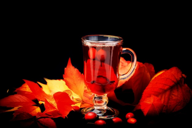 Tè caldo terapeutico con una rosa canina su uno sfondo di legno in stile rustico retrò physalis in un cestino