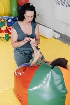 Terapeuta che fa esercizi sul tappetino con bambino disabile