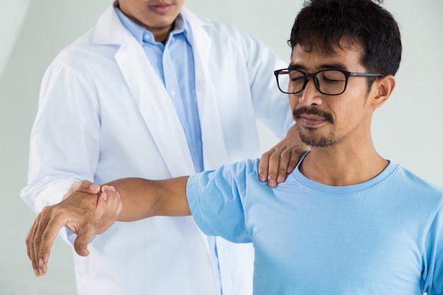 Terapista che fa il trattamento curativo sulla mano / spalla dell'uomo