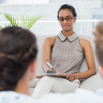 Terapista che parla con coppia sul divano e prende appunti