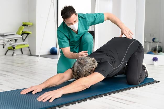 Terapista con maschera protettiva che assiste il paziente con esercizi di stretching.