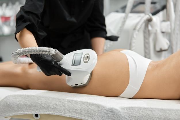 Terapista che lavora sulla zona della gamba femminile vicino ai glutei con un apparecchio professionale