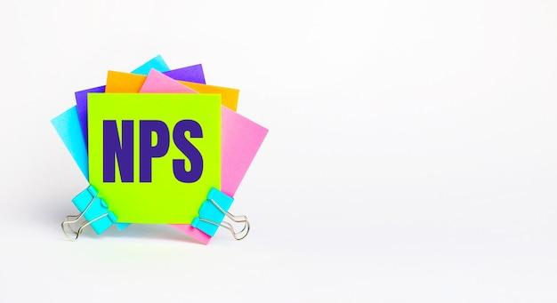 Ci sono adesivi luminosi multicolori con il testo nps net promoter score su uno sfondo bianco. copia spazio
