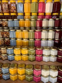 Ci sono molti vasetti di miele biologico e naturale sul bancone in vendita. miele diverso, colori diversi in lattine di plastica sono pronti per la vendita alla fiera del miele. noci ripiene di miele.